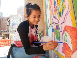 Young woman painting on wall