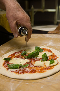 Joseph Migliucci, chef and owner of Mario's Restaurant, prepares pizza the way his father taught him.