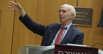 Economist Alan Blinder with outstretched arm at podium at Fordham