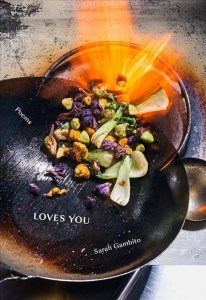"""Front cover of """"Loves You."""" Features a pan filled with food and flames."""