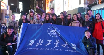 International students and Fordham students and staff standing in Times Square with a banner.