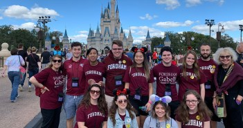Gabelli School of Business students pose for a group picture in front of Cinderella's castle in Disney World