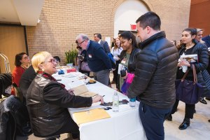 Lidia Bastianich signs copies of her book for a student standing in front of her, in the McNally Amphitheatre atrium