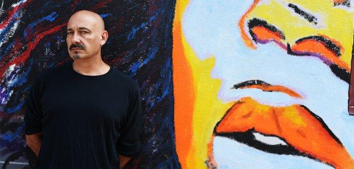 Portrait of Fordham grad Steve Romagnoli standing in front of a graffiti mural near his home in Bushwick, Brooklyn