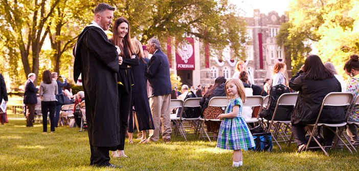 Little girl in blue dress facing man and woman in academic robes