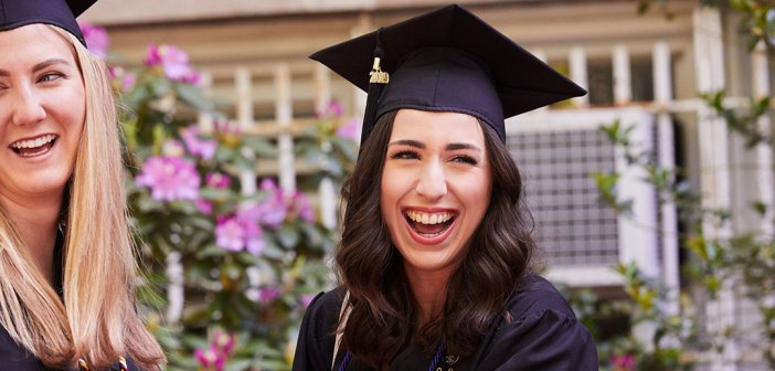 Close up of woman wearing a black academic cap laughing