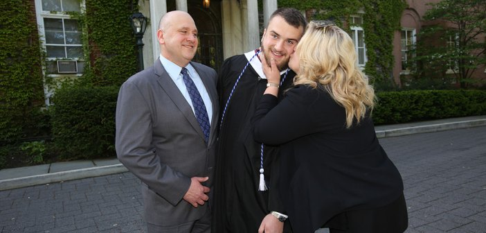 A woman kisses a student as a man looks on