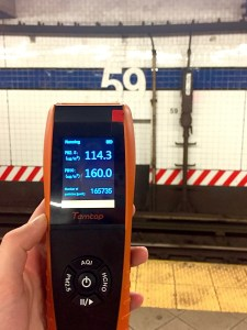 """A hand holding an orange device in front of a subway station wall that says """"59"""""""