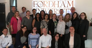 Members of the faculty who presented their research in London pose in front of a Fordham sign.