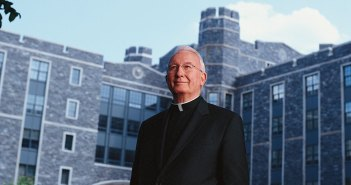 Father O'Hare in front of O'Hare Hall at Rose Hill