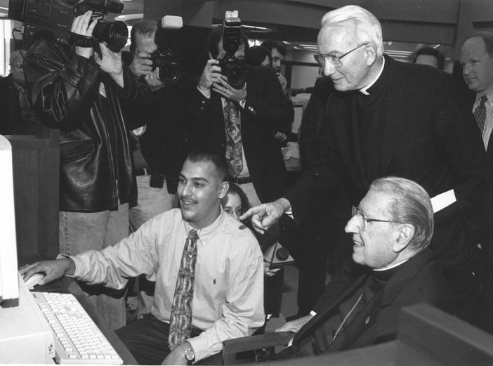 In 1997, John Cardinal O'Connor (right) blessed the William D. Walsh Family Library, then joined Father O'Hare and Mohammad Kahn (FCO '00) for a tour of the Vatican's website. Photo by Ken Levinson.