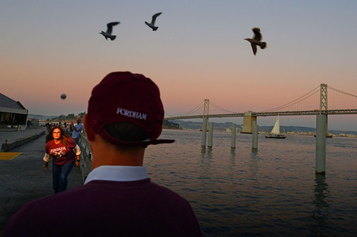 Fordham Law graduate Christina Chiaramonte practices bocce throws outside the Ferry Terminal Building on San Francisco's Embarcadero at dusk in October 2019, with three birds flying in the sky above and the Golden Gate Bridge and a sailboat visible in the background.
