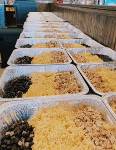 Platters filled with chicken, beans, and rice