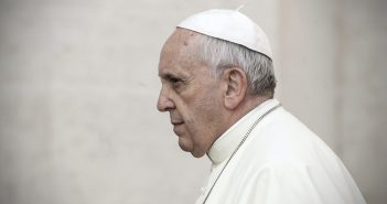 The Pope looks to the side in a serious manner.