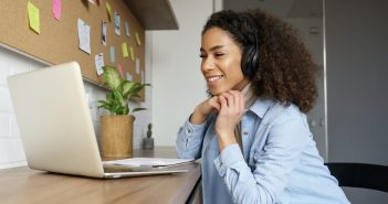 A woman with curly hair and a jean jacket is wearing headphones and is seated at a table in front of a laptop.