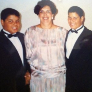 A woman stands between 12-year-old twin boys.