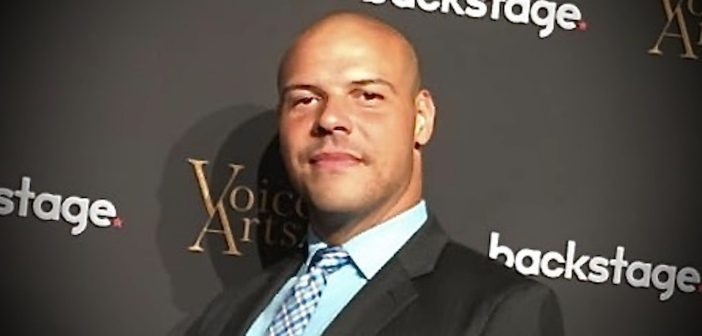 A man wearing a suit and tie smiles at the camera.