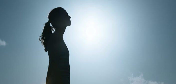 A black silhouette of a woman against a blue sky
