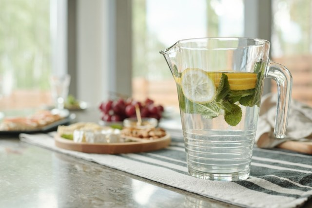 Close-up of a glassy pitcher of lemonade on stripped napkin prepared for a dinner party at home