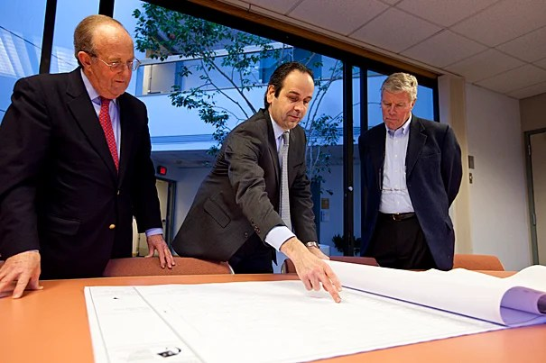 Earthwatch CEO Ed Wilson (center) goes over plans for the new headquarters with architect Jeffrey Brown (left) and Thomas Nicholson (right), a member of Earthwatch's board of directors. The nonprofit environmental group will reside at 114 Western Ave. in Allston, Mass.
