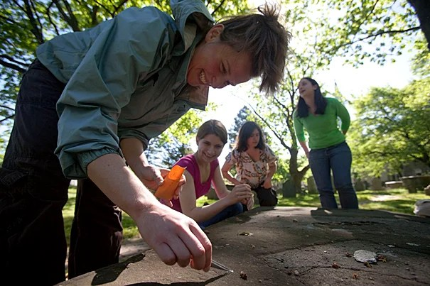 Rebecca Compton '09 (from left), Alexandra Mushegian '10, Professor Anne Pringle, and Kristi Fenstermacher '08 study lichen on Harvard gravestones.