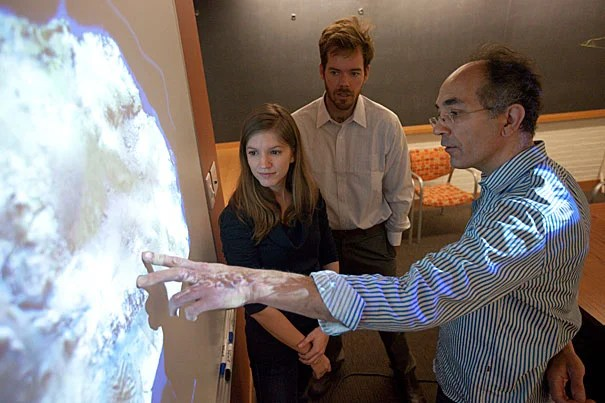 Jerry Mitrovica (right), Peter Huybers (white shirt), and graduate student Natalya Gomez (center), whose research illuminates the relationship between sea ice and climate change, look at a slide of the West Antarctic ice sheet. The researchers theorize that if the sheet melts, it will have the seemingly contradictory effect of lowering sea levels nearby, actually stabilizing the sheet.