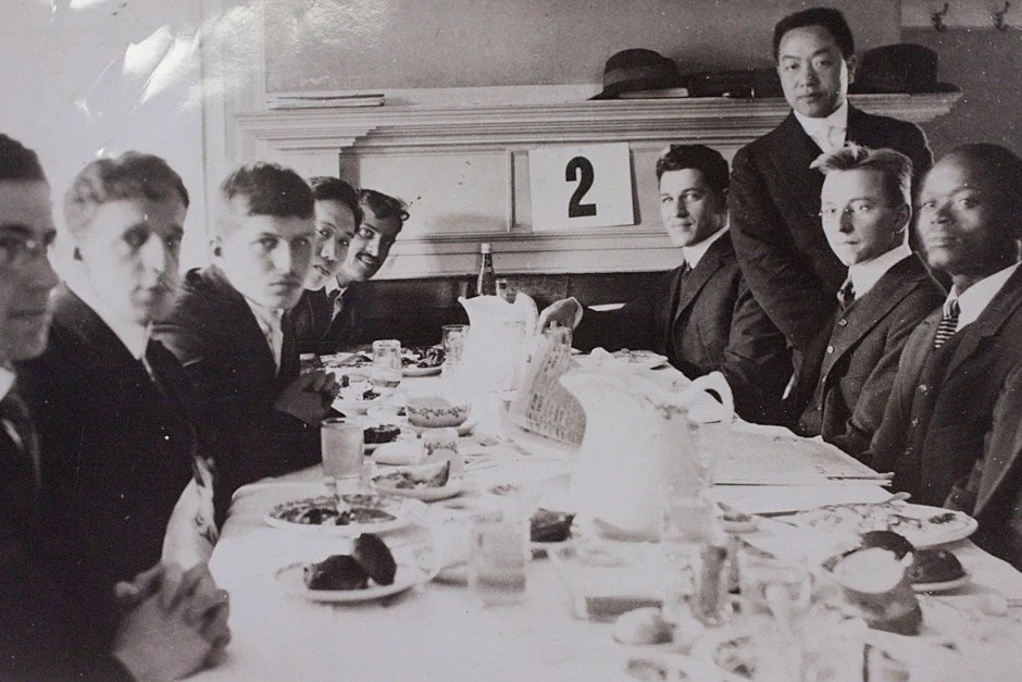 """Liberian student Plenyono Gbe Wolo, A.B. 1917 (far right), was the first Harvard College student from the African continent. He is seated at the """"cosmopolitan table"""" inside Foxcroft Hall at a Randall Hall Association meeting in 1914. Credit: Harvard University Archives, call # HUD 3404"""