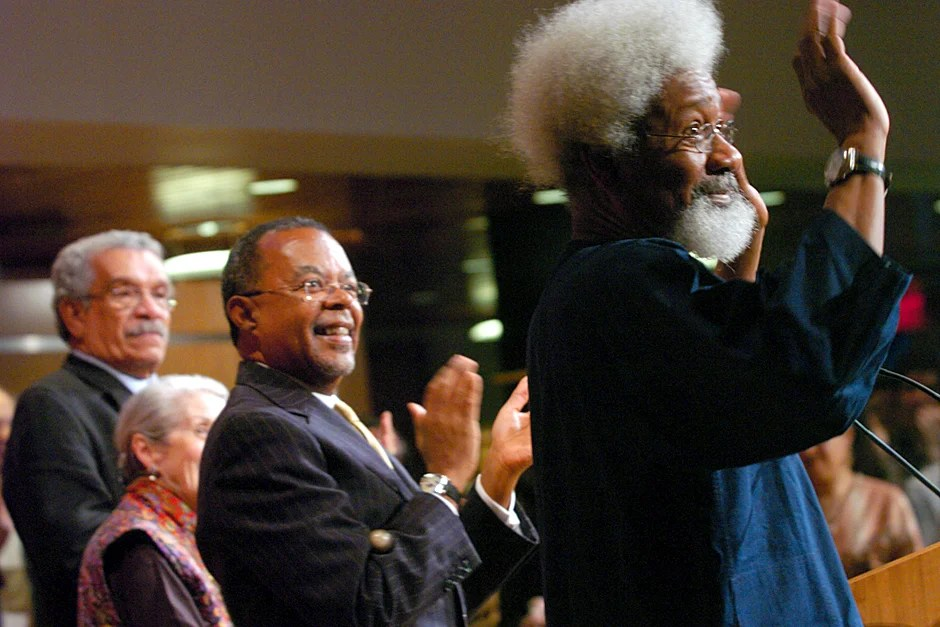"""April 27, 2005. """"A Season of Laureates: Readings in Honor of the 70th Birthday of Wole Soyinka"""" pays homage to literary giant and human rights activist Wole Soyinka (right), who receives a standing ovation from the crowd. Derek Walcott (from left), Nadine Gordimer, and Henry Louis Gates Jr. applaud. Photo by Stephanie Mitchell/Harvard Staff Photographer"""