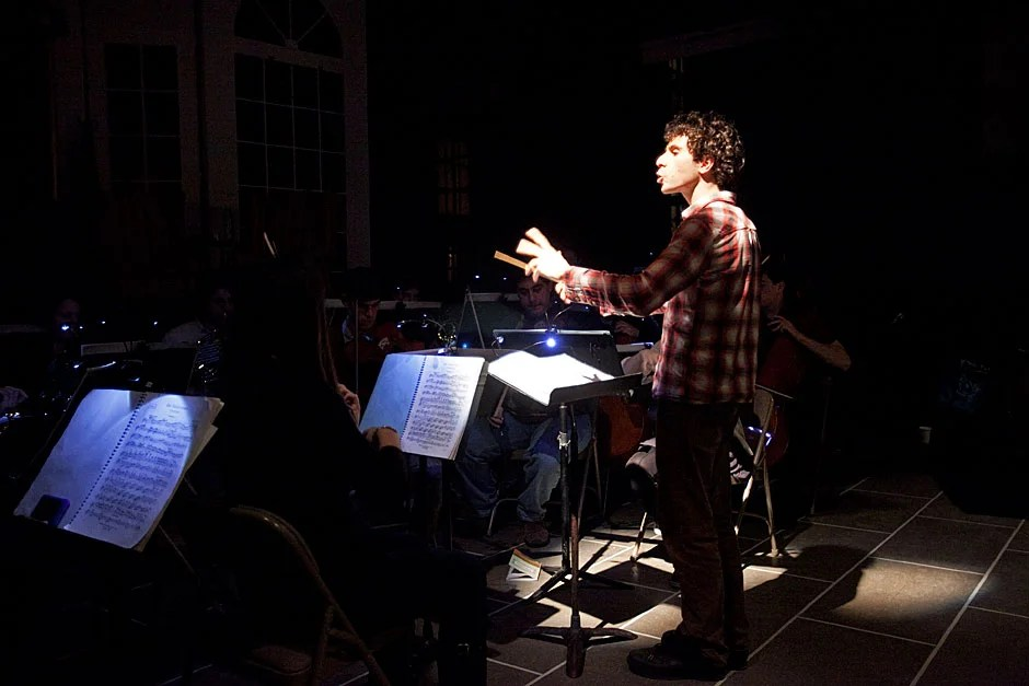 Music director Matt Aucoin '12 conducts the orchestra during a rehearsal. Jon Chase/Harvard Staff Photographer