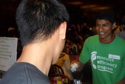 FAS Green Program student rep Dewahar Senthoor '13 scoops ice cream into a freshman's reusable mug.