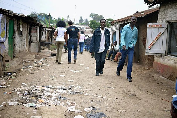 Rye Barcott (back to camera, right) along a corridor in Kibera's busy D.C. village. Barcott, along with two Kibera friends, founded Carolina for Kibera, a nonprofit that in July celebrated its 10th anniversary of intertribal soccer, female empowerment, trash collection, reproductive health education, and community medicine.