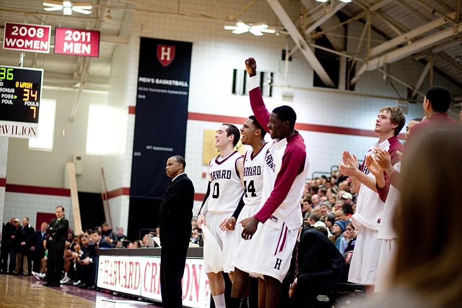 The Harvard bench, including coach Tommy Amaker (left), get enthused after Moundou-Missi's dunk.  Rose Lincoln/ Harvard Staff Photographer