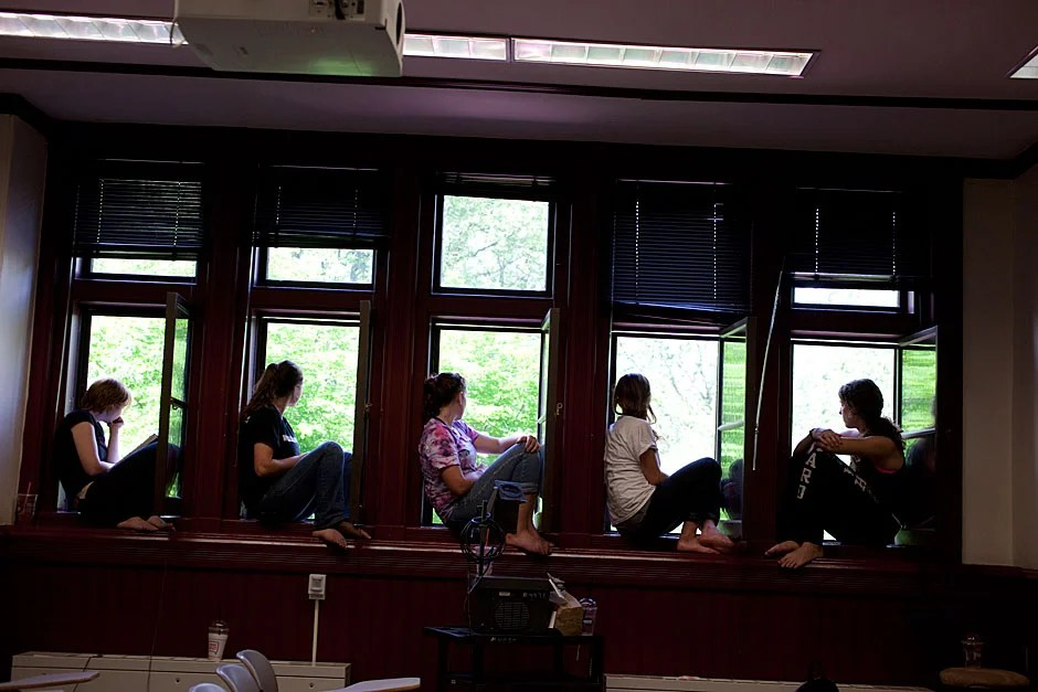 Miranda Shugars '14 (from left), Steph Hadley '15, Kathryn Reed '13, Leonie Oostrom '15, and Christine Mansour '15, all members of dorm crew, take a break to watch Commencement from the windows of Sever Hall. Rose Lincoln/Harvard Staff Photographer