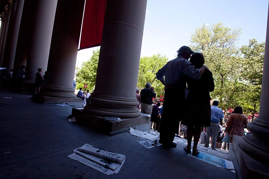 Patti Gwynne and Robert Ross, who are engaged to be married in July, watch from the steps of Widener Library as Ross' son, Kayvon Ross, graduates. Rose Lincoln/Harvard Staff Photographer