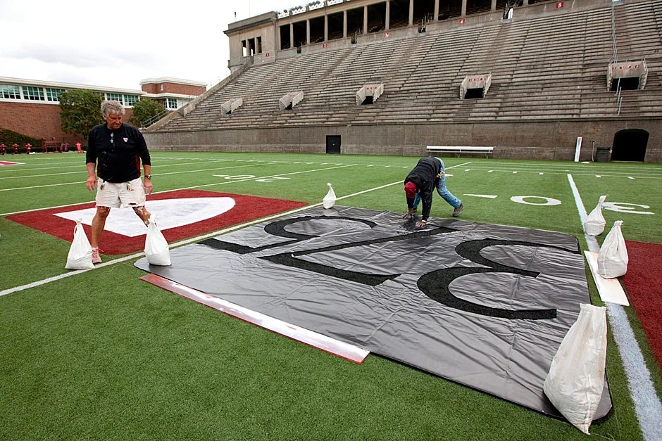 Workers paint 375 on the turf at Harvard Stadium to celebrate the University's 375th anniversary. Rose Lincoln/Harvard Staff Photographer