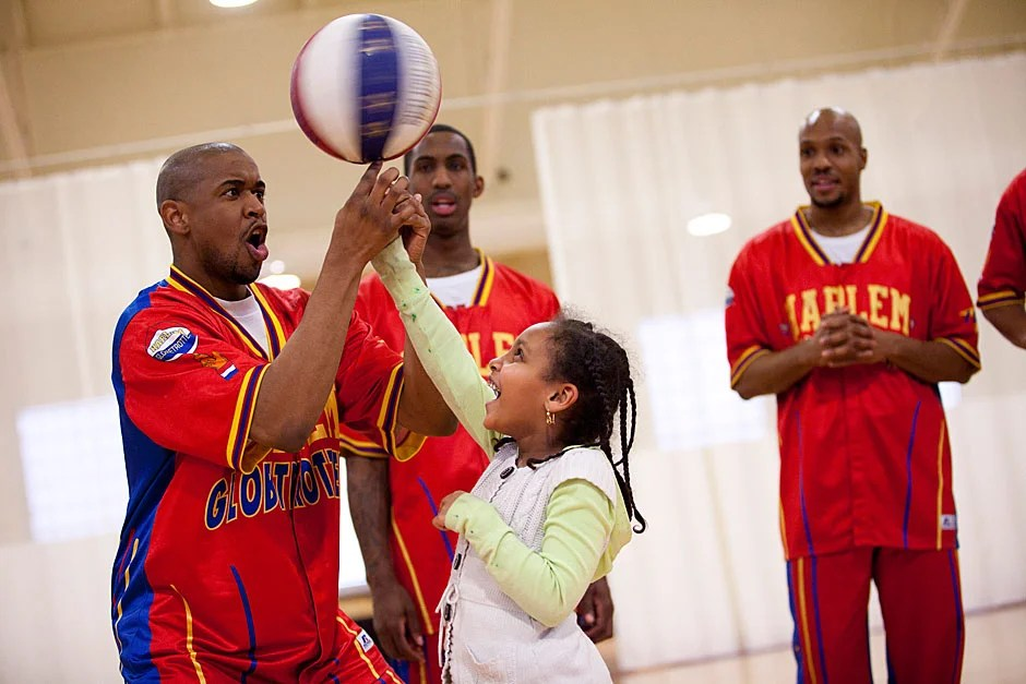 """Spinning balls and Harlem Globetrotters go together. Globetrotter """"Scooter"""" (from left) helps student Betunia Zelanlem learn to master the trick. Stephanie Mitchell/Harvard Staff Photographer"""