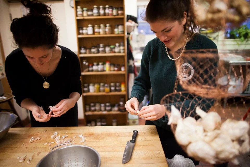 Harvard undergraduate students at the Dudley Co-op prepare meals for the House's 32 residents. Zoe Tucker '13, Charlotte Lieberman '13, and Xanthia Tucker '13 prepare a vegan dinner with chocolate cupcakes (decidedly non-vegan). Tucker (left) and Lieberman peel cloves of garlic for their recipe.