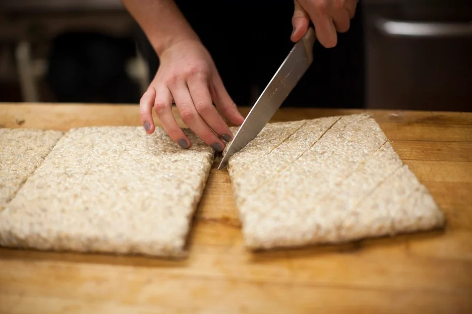 Zoe Tucker '13, one of the two co-op presidents, prepares tempeh, slicing the whole soybean slabs into rhombus-shaped pieces. She then marinates them with soy sauce and maple syrup before grilling.