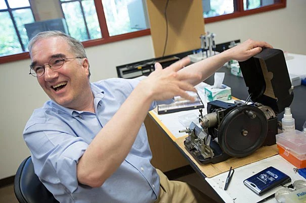 """Arnold Arboretum director William """"Ned"""" Friedman works with an old tissue slicer called a microtome. Built in 1931, it is still in use in the Arboretum's lab."""