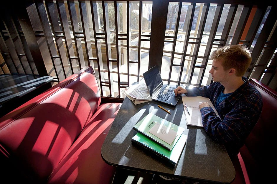 With light pouring through slats inside Quincy House, Kyle Rawding '14 uses his laptop to study. Kris Snibbe/Harvard Staff Photographer