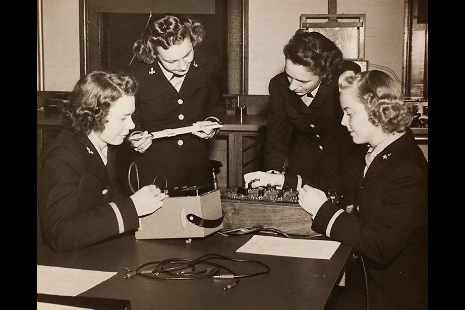 Copy image of historical material gathered from Harvard University Archives regarding the university's history with ROTC. Inscription on image verso reads, Navy, L to R, Ensigns E. Schwerin, Norma Meyer, Olga Quadland, and Edith Paulsen, Engineering 263-5 Course at Pierce Hall, October 23, 1943. Stephanie Mitchell/Harvard Staff Photographer