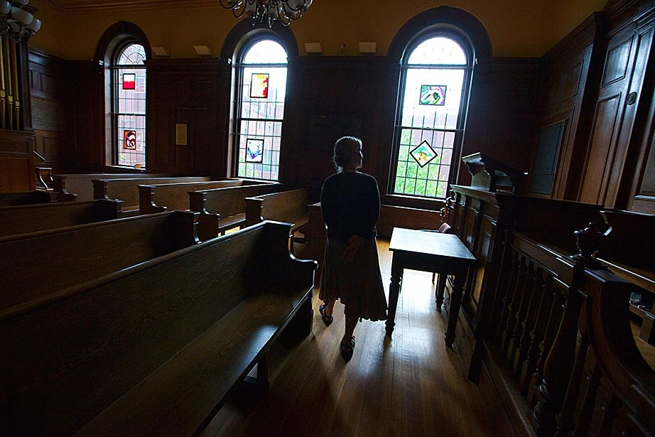 Staff assistant Bronwen Murphy walks through the Emerson Room as it looked in 2011. The benches have been taken out and now line the hallways of Divinity Hall; chairs, more easily moved, now occupy the space.