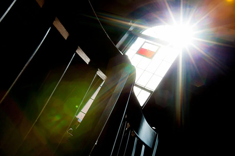 A starburst of light shines through a window in Divinity Hall.