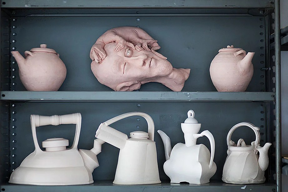 Bisque-fired and glazed ceramic pieces are found throughout the studio.