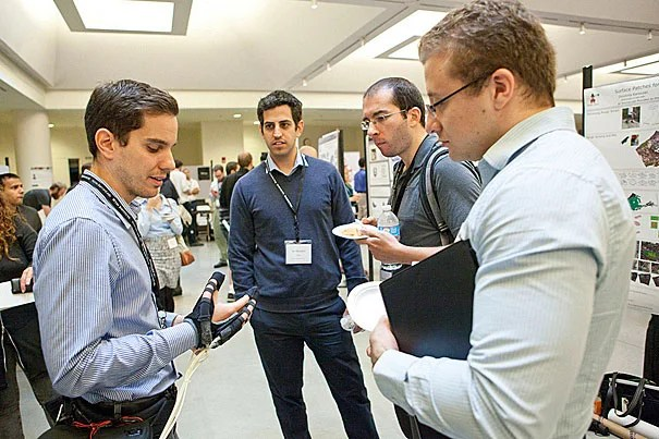 "At the Northeast Robotics Colloquium, Panagiotis Polygerinos (left), a postdoc fellow at the Wyss Institute, demonstrated a robotic hand, which can provide more grip and strength than a normal hand would (photo 1). SEAS postdoc Sawyer B. Fuller displayed a ""robotic insect"" (photo 2). Paul Loschak, an SEAS grad student, demonstrated his cardiac imaging catheter (photo 3)."