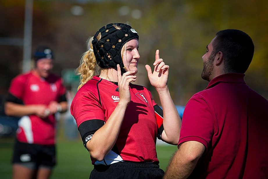 Helen Clark passes an on-field concussion test administered by athletic trainer Corey Lanois during the Princeton game. Helmets are not required but some players wear them to protect against cauliflower ear, a complication resulting from ear injuries.
