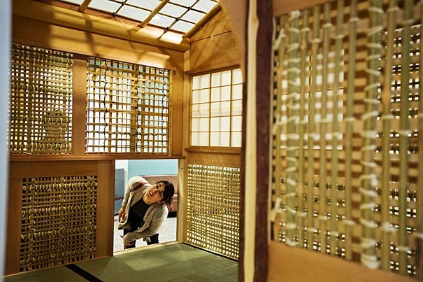 """GSD student Joanna Rodriguez-Noyola examines a Japanese tea house (photo 1) set up at Harvard's CGIS for """"The Thinking Hand"""" exhibit. Akinori Abo, a master carpenter from Japan, demonstrates the tools, techniques, and woods of traditional Japanese carpentry (photos 2 and 3)."""