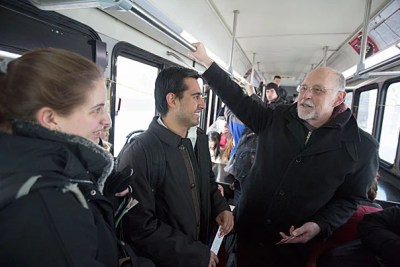 """Interim College Dean Donald H. Pfister invited students to ride the shuttle from Memorial Hall to the river Houses. As the shuttle flashed """"Dean on Board,"""" Caroline Brennan '15 (from left, photo 1) and Sergio Morales '15 weren't shy about approaching Pfister. David Hu '16 (photo 2), Kenyatta Smith '15 (from left, photo 3), and Leah Singer '16 also talked to Pfister, who was handing out bookmarks with his office hours on the back."""
