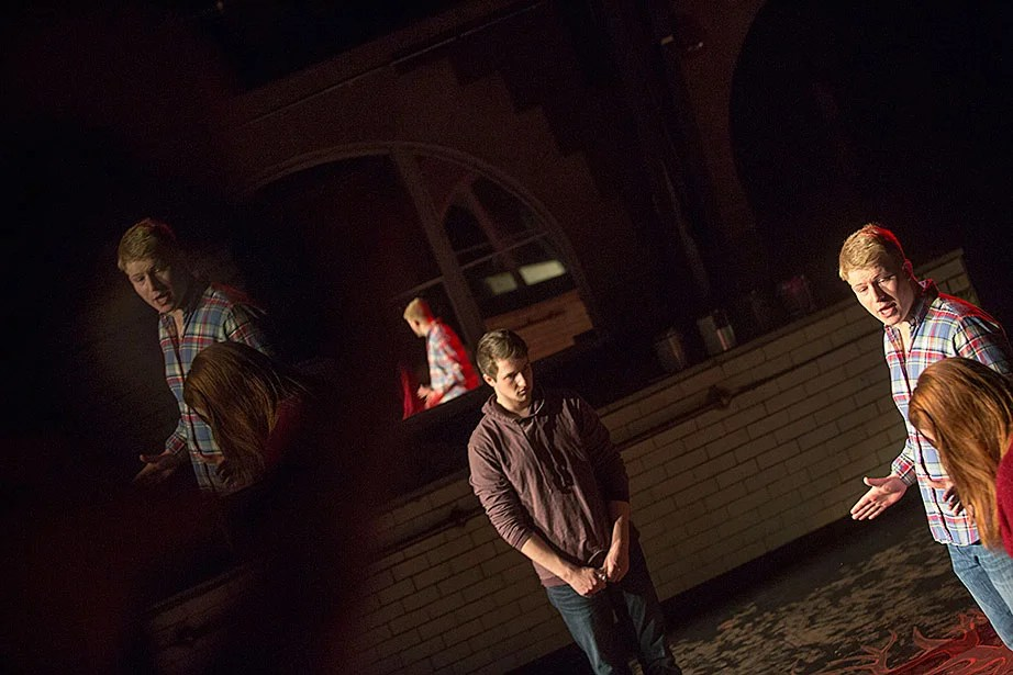 """Matt Bialo '15 (from center to right), Jonathan """"J.J."""" Longcroft '15, and Taylor Phillips '13 rehearse """"In the Dark"""" inside the Adams House Pool Theater."""