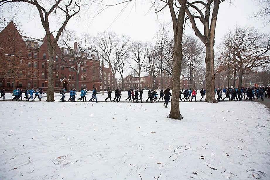 Eliot House residents race across the Yard to the John Harvard statue. Rose Lincoln/Harvard Staff Photographer